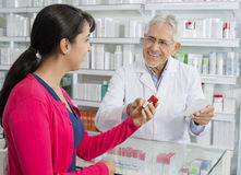 Ανώτεροι φαρμακοποιός και γυναίκα με τη συνταγή στο φαρμακείο στοκ εικόνες με δικαίωμα ελεύθερης χρήσης