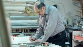 Ανώτερος άνδρας εργαζόμενος στο workshope πίσω από το μετρητή που γράφει κάτω απόθεμα βίντεο
