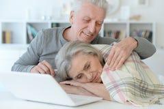 Ανώτερος άνδρας που αγκαλιάζει την όμορφη ανώτερη γυναίκα με το κάλυμμα που κοιμούνται Στοκ φωτογραφία με δικαίωμα ελεύθερης χρήσης