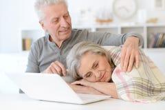 Ανώτερος άνδρας που αγκαλιάζει την όμορφη ανώτερη γυναίκα με το κάλυμμα που κοιμούνται Στοκ Φωτογραφίες