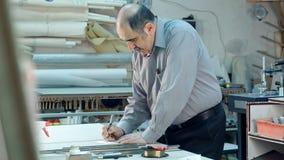 Ανώτερος άνδρας εργαζόμενος στο workshope πίσω από το μετρητή που γράφει κάτω Στοκ Φωτογραφίες