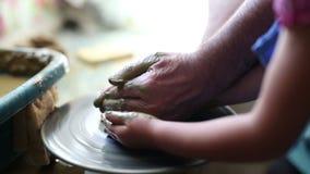 Ανώτερος αγγειοπλάστης που διδάσκει στο ευτυχές μικρό κορίτσι την τέχνη της αγγειοπλαστικής απόθεμα βίντεο