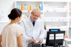 Ανώτερος αποθηκάριος με τη συνταγή στο φαρμακείο στοκ εικόνα με δικαίωμα ελεύθερης χρήσης
