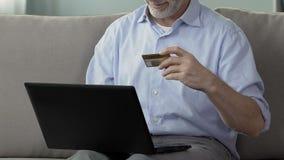 Ανώτερος αρσενικός αριθμός πιστωτικής κάρτας δακτυλογράφησης στον υπολογιστή, σε απευθείας σύνδεση πληρωμή, αγορές απόθεμα βίντεο