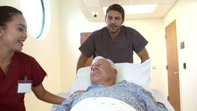 Ανώτερος αρσενικός ασθενής που είναι τροχοφόρος κατά μήκος του διαδρόμου νοσοκομείων απόθεμα βίντεο