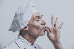 Ανώτερος αρσενικός κύριος μάγειρας σε ομοιόμορφο στο γκρίζο υπόβαθρο Στοκ εικόνες με δικαίωμα ελεύθερης χρήσης