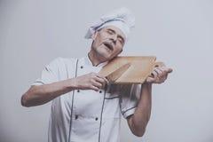 Ανώτερος αρσενικός κύριος μάγειρας στο ομοιόμορφο μαχαίρι εκμετάλλευσης και τεμαχίζοντας πίνακας α στο γκρίζο υπόβαθρο Στοκ εικόνα με δικαίωμα ελεύθερης χρήσης