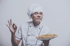 Ανώτερος αρσενικός κύριος μάγειρας στο ομοιόμορφο gesturing εντάξει σημάδι και το κράτημα της πίτσας στο γκρίζο υπόβαθρο Στοκ εικόνες με δικαίωμα ελεύθερης χρήσης