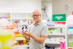 Ανώτερος αρσενικός πελάτης με το φάρμακο στο φαρμακείο Στοκ φωτογραφία με δικαίωμα ελεύθερης χρήσης