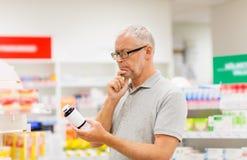 Ανώτερος αρσενικός πελάτης με το φάρμακο στο φαρμακείο Στοκ εικόνα με δικαίωμα ελεύθερης χρήσης
