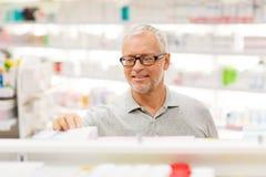 Ανώτερος αρσενικός πελάτης με το φάρμακο στο φαρμακείο Στοκ εικόνες με δικαίωμα ελεύθερης χρήσης