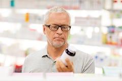 Ανώτερος αρσενικός πελάτης με το φάρμακο στο φαρμακείο Στοκ Φωτογραφία