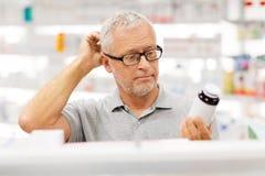 Ανώτερος αρσενικός πελάτης με το φάρμακο στο φαρμακείο στοκ εικόνες