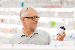 Ανώτερος αρσενικός πελάτης με το φάρμακο στο φαρμακείο στοκ εικόνα