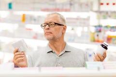 Ανώτερος αρσενικός πελάτης που επιλέγει τα φάρμακα στο φαρμακείο Στοκ Εικόνα