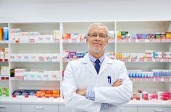 Ανώτερος αρσενικός φαρμακοποιός στο άσπρο παλτό στο φαρμακείο στοκ εικόνα