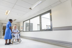 Ανώτερος ασθενής θηλυκών στην αναπηρική καρέκλα & νοσοκόμα στο νοσοκομείο Στοκ Φωτογραφίες