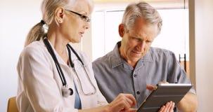 Ανώτερος γιατρός γυναικών που εκφράζει τις ανησυχίες υγείας με τον ηλικιωμένο ασθενή ανδρών στοκ εικόνες