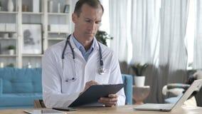 Ανώτερος γιατρός που διαβάζει τα ιατρικά έγγραφα του ασθενή απόθεμα βίντεο