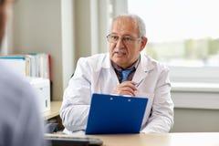 Ανώτερος γιατρός που μιλά στον αρσενικό ασθενή στο νοσοκομείο στοκ φωτογραφίες