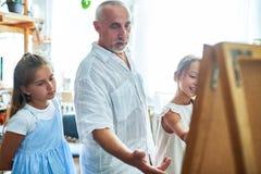 Ανώτερος δάσκαλος τέχνης που βοηθά τα παιδιά στο στούντιο Στοκ εικόνα με δικαίωμα ελεύθερης χρήσης
