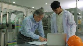 Ανώτερος διευθυντής με το μηχανικό εργαζόμενο που ελέγχει στα σχέδια παραγωγής με τη γραμμή παραγωγής μπουκαλιών στο υπόβαθρο απόθεμα βίντεο