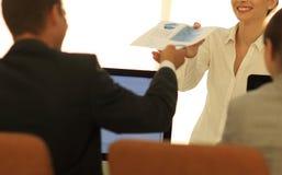 Ανώτερος διευθυντής, που δίνει στον υπάλληλο ένα έγγραφο με τα οικονομικά στοιχεία Στοκ εικόνα με δικαίωμα ελεύθερης χρήσης