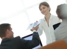 Ανώτερος διευθυντής, που δίνει στον υπάλληλο ένα έγγραφο με τα οικονομικά στοιχεία Στοκ Εικόνες