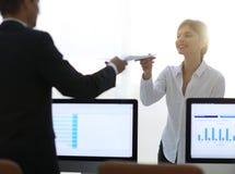 Ανώτερος διευθυντής, που δίνει στον υπάλληλο ένα έγγραφο με τα οικονομικά στοιχεία Στοκ Εικόνα