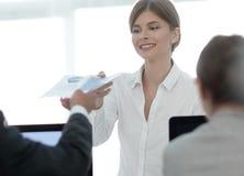 Ανώτερος διευθυντής, που δίνει στον υπάλληλο ένα έγγραφο με τα οικονομικά στοιχεία Στοκ Φωτογραφίες