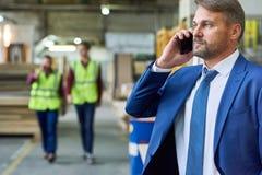 Ανώτερος διευθυντής που μιλά τηλεφωνικώς στο εργοστάσιο Στοκ Φωτογραφίες