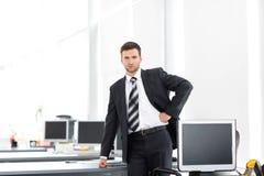 Ανώτερος διευθυντής που στέκεται σε ένα σύγχρονο γραφείο πριν από την έναρξη της εργάσιμης ημέρας Στοκ εικόνα με δικαίωμα ελεύθερης χρήσης