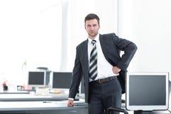 Ανώτερος διευθυντής που στέκεται σε ένα σύγχρονο γραφείο πριν από την έναρξη της εργάσιμης ημέρας Στοκ φωτογραφία με δικαίωμα ελεύθερης χρήσης