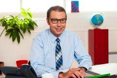 Ανώτερος διευθυντής Bespectacled που εργάζεται στο γραφείο του Στοκ φωτογραφία με δικαίωμα ελεύθερης χρήσης
