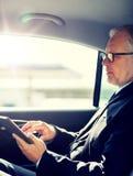 Ανώτερος επιχειρηματίας με την οδήγηση PC ταμπλετών στο αυτοκίνητο στοκ φωτογραφία