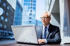 Ανώτερος επιχειρηματίας με το lap-top στον καφέ οδών πόλεων Στοκ Φωτογραφία