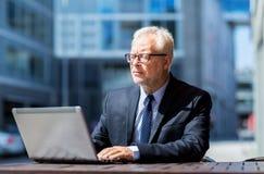 Ανώτερος επιχειρηματίας με το lap-top στον καφέ οδών πόλεων Στοκ εικόνες με δικαίωμα ελεύθερης χρήσης