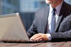 Ανώτερος επιχειρηματίας με το lap-top στον υπαίθριο καφέ Στοκ Φωτογραφίες
