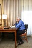 Ανώτερος επιχειρηματίας που εργάζεται στο δωμάτιο ξενοδοχείου Στοκ Εικόνες
