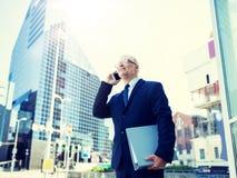 Ανώτερος επιχειρηματίας που καλεί το smartphone στην πόλη στοκ εικόνες