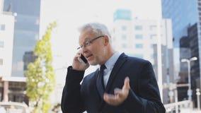 Ανώτερος επιχειρηματίας που καλεί το smartphone στην πόλη φιλμ μικρού μήκους