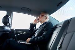 Ανώτερος επιχειρηματίας που καλεί το smartphone στο αυτοκίνητο Στοκ Εικόνες