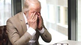 Ανώτερος επιχειρηματίας που τρίβει τα κουρασμένα μάτια του μετά από μια μακροχρόνια εργασία για την ταμπλέτα σας φιλμ μικρού μήκους