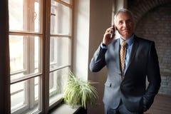 Ανώτερος επιχειρηματίας στο κοστούμι με το smartphone Στοκ Φωτογραφία