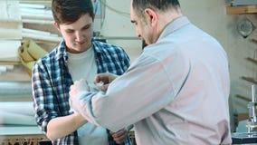 Ανώτερος εργαζόμενος που βάζει έναν επίδεσμο στην πληγή στο δάχτυλο του νέου εκπαιδευόμενου στο εργαστήριο πλαισίων απόθεμα βίντεο