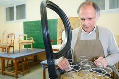 Ανώτερος εργαζόμενος που επισκευάζει την καρέκλα στο εργαστήριο Στοκ Φωτογραφίες