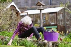 Ανώτερος ηλικιωμένος ενεργός τρόπος ζωής προσώπων στον κήπο κατά τη διάρκεια της φωτεινής ζωηρόχρωμης ηλιοφάνειας άνοιξης και της στοκ εικόνα