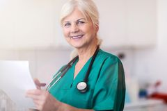 Ανώτερος θηλυκός γιατρός που χαμογελά στη κάμερα στοκ φωτογραφία