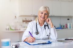 Ανώτερος θηλυκός γιατρός που χαμογελά στη κάμερα στοκ εικόνες