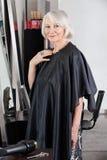 Ανώτερος θηλυκός πελάτης που στέκεται στο σαλόνι στοκ φωτογραφία